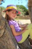 Mädchen, das auf einem Baumkabel sitzt Stockfotografie