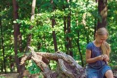 Mädchen, das auf einem Baumstumpf sitzt lizenzfreie stockbilder