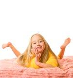 Mädchen, das auf einem Bett liegt Stockbilder