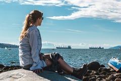 Mädchen, das auf einem Felsen an Kitsilano-Strand in Vancouver, Kanada sitzt stockbilder