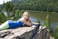 Mädchen, das auf einem Felsen liegt und Flussansicht genießt Stockbild