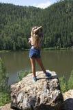 Mädchen, das auf einem Felsen steht und Flussansicht genießt Lizenzfreie Stockbilder