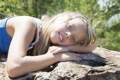 Mädchen, das auf einem Felsen und einem Genießen liegt Stockbild