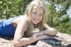 Mädchen, das auf einem Felsen und einem Genießen liegt Stockbilder