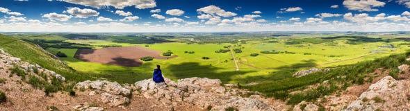 Mädchen, das auf einem Felsenberg sitzt Stockfoto