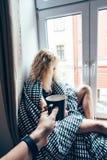 Mädchen, das auf einem Fenster in einer Decke sitzt Stockfoto
