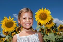 Mädchen, das auf einem Gebiet der Sonnenblumen steht Stockbilder