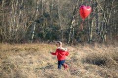 Mädchen, das auf einem Gebiet hält Herz-förmigen Ballon geht lizenzfreie stockbilder