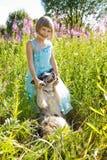 Mädchen, das auf einem Gebiet von Blumen spielt Lizenzfreies Stockfoto