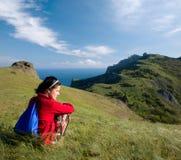 Mädchen, das auf einem Hügel über Meer sitzt Lizenzfreie Stockfotografie
