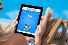 Mädchen, das auf einem Klappstuhl durch das Pool liegt und eine Tablette mit hält Lizenzfreie Stockfotografie