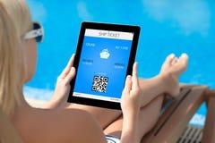 Mädchen, das auf einem Klappstuhl durch das Pool liegt und eine Tablette mit hält Stockfoto