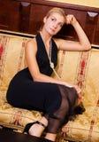 Mädchen, das auf einem Luxuxsofa sitzt Stockfoto