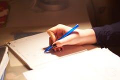 Mädchen, das auf einem Papierblatt Blätter treibt Lizenzfreies Stockfoto