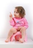Mädchen, das auf einem rosa Topf sitzt Stockfotos