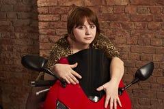 Mädchen, das auf einem roten Motorrad sitzt Stockfotos