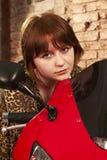 Mädchen, das auf einem roten Motorrad sitzt Stockbild
