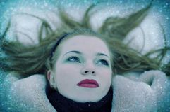 Mädchen, das auf einem Schnee liegt Stockbild