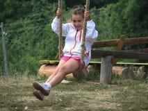 Mädchen, das auf einem Seilschwingen schwingt stockfotografie