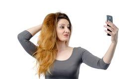 Mädchen, das auf einem Smartphone auf Weiß sich fotografiert Stockfotos