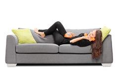 Mädchen, das auf einem Sofa liegt und am Weinlesetelefon spricht Stockfotos