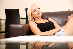 Mädchen, das auf einem Sofa sich entspannt Stockfotos
