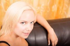 Mädchen, das auf einem Sofa sich entspannt Lizenzfreies Stockfoto