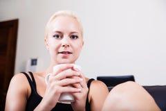 Mädchen, das auf einem Sofa trinkt einen Tasse Kaffee sich entspannt Stockbild