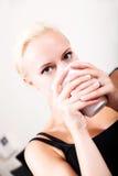 Mädchen, das auf einem Sofa trinkt einen Tasse Kaffee sich entspannt Lizenzfreie Stockbilder