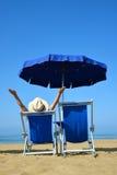 Mädchen, das auf einem Sonnenruhesessel unter einem Regenschirm auf sandigem Strand liegt Stockfoto