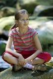 Mädchen, das auf einem Stein sitzt Stockfotografie