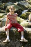 Mädchen, das auf einem Stein sitzt Lizenzfreies Stockfoto