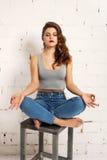 Mädchen, das auf einem Stuhl in der Yogahaltung sitzt Weiße Backsteinmauer, nicht Stockbild