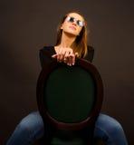 Mädchen, das auf einem Stuhl sitzt Lizenzfreie Stockfotos