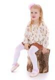 Mädchen, das auf einem Stumpf sitzt Stockbilder