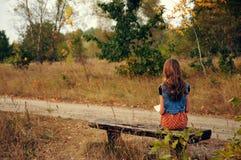 Mädchen, das auf einen Bus in der Landschaft wartet stockfotografie