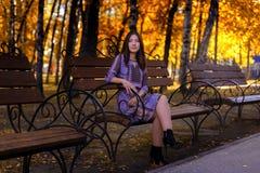 Mädchen, das auf einer Bank im Herbst Park sitzt lizenzfreie stockfotos