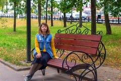 Mädchen, das auf einer Bank im Herbst Park sitzt stockfotografie