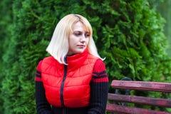 Mädchen, das auf einer Bank im Park sitzt stockfotos