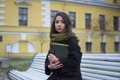 Mädchen, das auf einer Bank mit einem Buch sitzt Lizenzfreies Stockfoto
