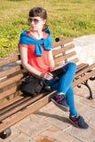 Mädchen, das auf einer Bank nahe dem Meer sitzt Stockfotos