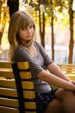 Mädchen, das auf einer Bank sitzt Lizenzfreie Stockfotos