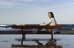 Mädchen, das auf einer Bank am Strand sitzt lizenzfreie stockfotografie