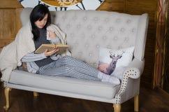 Mädchen, das auf einer Couch sitzt Lizenzfreie Stockbilder