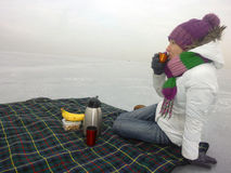 Mädchen, das auf einer Decke im Winter am Eisfeld, in der Kälte, im Schnee und im Trinkbecher des warmen Tees sitzt Lizenzfreies Stockbild
