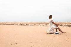 Mädchen, das auf einer Fischenboje auf der sandigen Küste des Meeres sitzt Stockbilder