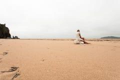 Mädchen, das auf einer Fischenboje auf der sandigen Küste des Meeres sitzt Stockfotografie