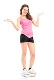 Mädchen, das auf einer Gewichtsskala und -c$gestikulieren steht Lizenzfreie Stockfotos
