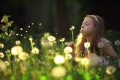 Mädchen, das auf einer Löwenzahnblume durchbrennt lizenzfreies stockbild