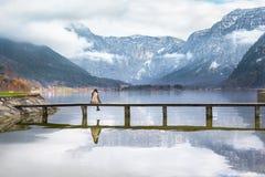 Mädchen, das auf einer Plattform über einem See sitzt stockbilder